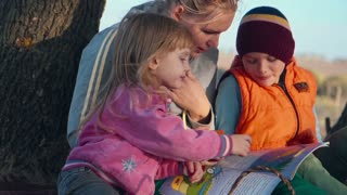 Slowmotion Full Length of Woman with Two Children Sitting Underneath Tree with Warm Beverage in Metal Thermos - Stopping to Enjoy a Hot Drink Outdoors in Early Evening