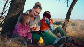 Slowmotion Full Length of Woman with Two Children Sitting Underneath Tree with Warm Beverage - Stopping to Enjoy a Hot Drink Outdoors in Early Evening