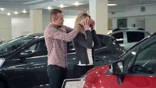Slowmotion Man Standing Behind Woman and Covering Her Eyes While Standing in front of Shiny New Red Vehicle Inside Car Dealership