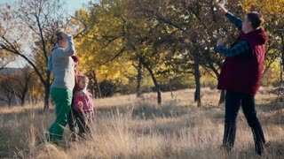Slowmotion of family of 4 making photo in autumn park using a smartphone