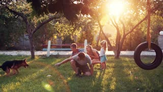 Slowmotion of happy young parents playing with puppy dog and children at park with sunlight shining over small trees and tire swing