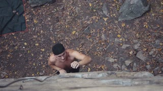 Slowmotion of topless young climber in black cap ascending cliff and showing thumb up with smile. It is very hard and it is difficult