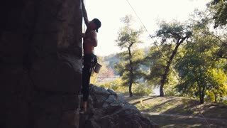 Slowmotion, side view of young climber ascending cliff with rope and carabiners against sky then he breaks down