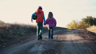Slowmotion Two young children walking away from the camera along a rural dirt road in evening light holding hands with the little boy taking care of his toddler sister. Then he start to play football