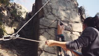 Slowmotion wide view of topless professional climber in cap ascending the cliff while woman belaying him. Sunny park