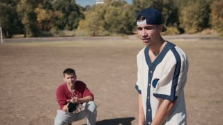 Slowmotion Young Male Batter Standing Ready for Pitch with Baseball Bat Over Shoulder During Casual Baseball Game in Sunny Field with Catcher Crouching in Background in Summer Time