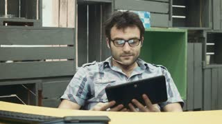 Smiling adult worker using tablet and talking on it while sitting in office at table