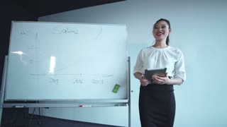 Smiling asian woman standing at the board and speaking about diagram drawn on it