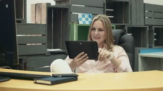 Smiling blonde woman in office chair using tablet to make video call