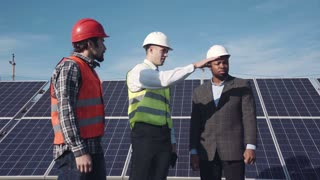 Solar panel workers and manager in red and white hard hats standing and talking and handshaking outside with large power arrays behind them