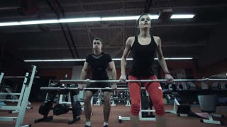 Strong athletic couple working out in a gym together lifting weights, close up low angle view showing the effort and determination in lifting the bars and their muscular physiques