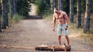Strong shirtless muscular man lifting a log on a forest road showing off his toned athletic physique, receding view along the dirt track