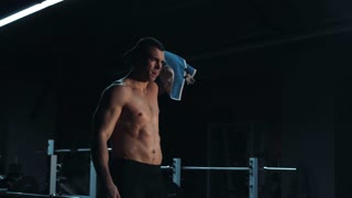 Strong toned young athlete towelling off in a gym wiping away sweat after doing a strenuous workout showing off his muscular physique, with copy space
