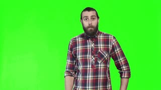 Surprised or shocked bearded man staring wide eyed at the camera with his hand to his chest , upper body with copy space on a bright green background, 4K shot