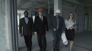 Team of builders in suits, hard hat, move, look directly into camera. Black man, aged engineer architect with female assistant and sales manager walk inside unfinished multi storey construction site