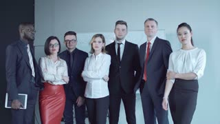 Team of businesspeople standing together in conference room and react to bad news as if just learned inconvenient information that upset them