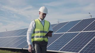 Technician walks beside array of solar panels while wearing hard hat and holds computer digital tablet