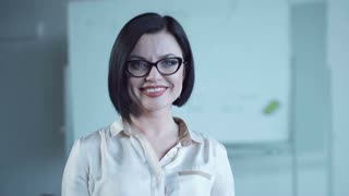 The beautiful dark-haired business woman wearing eyeglasses and a blouse, smiles and looks in the camera. The camera moves around it