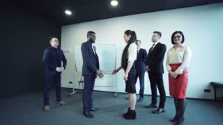The black businessman shakes hands with the colleague the Asian business woman, against the background of the applauding colleagues. They reached the agreement and signed the contract