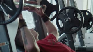 The bodybuilder does exercise with a bar