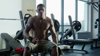 The bodybuilder does exercise with dumbbells