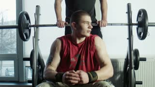 The bodybuilders does exercise with a bar