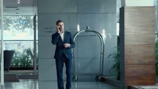 Handsome businessman in suit speaks by phone indoor