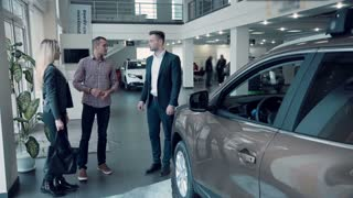 The car sales manager in a suit, suggests the client to sit down in the car to look at its interior and quality. Possibly it is sale of the electric vehicle