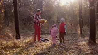 The family has fun in autumn park and throw leaves up