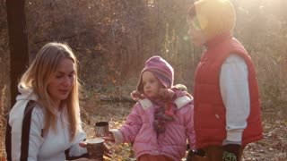 The family has tea in autumn park