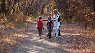 Mother and her two children walking in park with bike