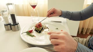 the female and male eat tasty multi-colored salad from big white plates using knife and fork at expensive luxury restaurant. Movement stabilizer shot