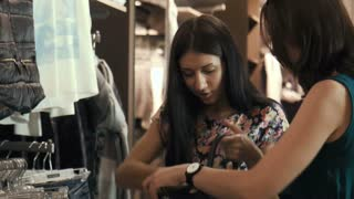 Two beautiful girl choosing clothes in store