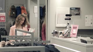 The girl buys a dress and pays off with a credit card