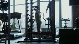 Silhouette of the woman does exercises in a gym