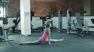 The girl does fitness exercise for body stretching