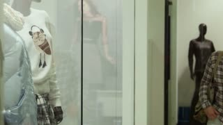 The girl looks at a show-window of clothing store in mall