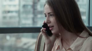 The girl speaks by phone and uses the touchpad