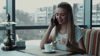 The girl speaks by phone in cafe and drink tea