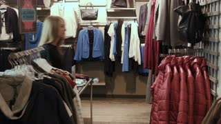 The girl tries on a red jacket in clothes store