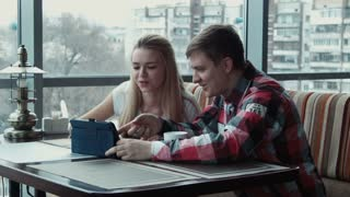 The guy shows something on the touchpad to the girl in cafe