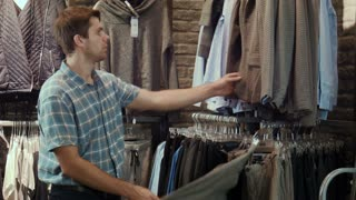 The guy tries on a jacket in clothes store