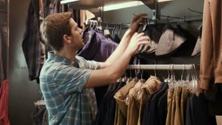 The guy tries on clothes near a mirror