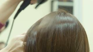 The hairdresser dries hair