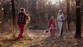 The happy family walks in autumn park and throw a yellow fallen leaf