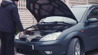 the man checks the engine in a car