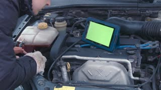 The man checks the engine using the touchpad with greenscreen