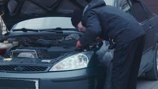 The man repairs a xenon headlight and checks