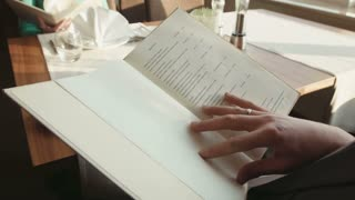 The man watches the menu at restaurant of hotel