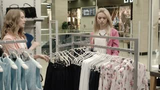 Girls choosing dress on hangs in clothes store
